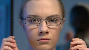 Insecure female teenager wearing eyeglasses, defocused vision effect, close-up. Stock footage stock video