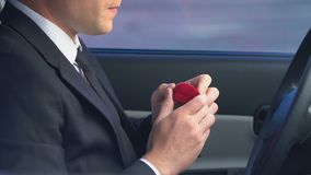 Insecure man holding wedding ring sitting in car, overcoming engagement anxiety. Stock footage stock video footage