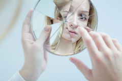 Insecure pretty woman. Insecure pretty young woman holding broken mirror Stock Images