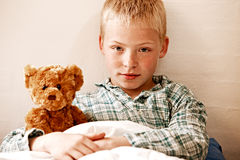 Insecure young boy cuddling his teddy bear Royalty Free Stock Image
