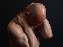 Insecurity. A shirtless bald male adult grips at his head and neck over a black background Stock Photos