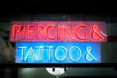 Insegna al neon con Piercing & tatuaggio alla notte. Fotografia Stock