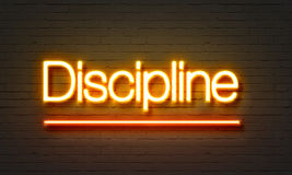 Insegna al neon di disciplina sul fondo del muro di mattoni immagini stock libere da diritti