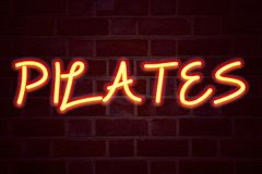 Insegna al neon di Pilates sul fondo del muro di mattoni Segno fluorescente del tubo al neon sul concetto di affari della muratur Fotografia Stock