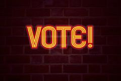 Insegna al neon di voto sul fondo del muro di mattoni Il segno fluorescente del tubo al neon sul concetto di affari della muratur Immagini Stock