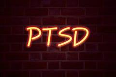 Insegna al neon post - traumatica di disordine di sforzo di PTSD sul fondo del muro di mattoni Segno fluorescente del tubo al neo Immagini Stock