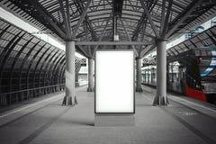 Insegna bianca in bianco alla stazione della metropolitana con il treno arrivato su un fondo fotografia stock