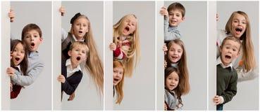 Insegna con i bambini sorpresi che danno una occhiata al bordo fotografia stock libera da diritti