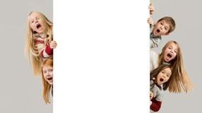 Insegna con i bambini sorpresi che danno una occhiata al bordo immagine stock