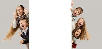 Insegna con i bambini sorpresi che danno una occhiata al bordo fotografie stock libere da diritti