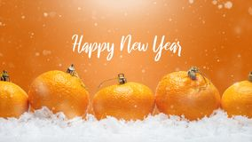 Insegna con i mandarini sotto forma di decorazioni di Natale sulla neve, con neve di caduta Natale felice o buon anno, fotografia stock libera da diritti
