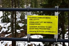 Insegna d'avvertimento del metallo giallo contro il fondo di vista della foresta di inverno fotografia stock libera da diritti