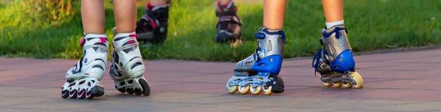 Insegna dei bambini piccoli che guidano i pattini di rullo nella città chiuda sulle gambe immagini stock libere da diritti