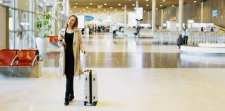 Insegna della giovane donna con valise che cammina nel corridoio aspettante all'aeroporto immagine stock