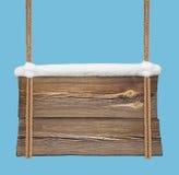 Insegna di legno con neve che appende sulle doppie corde Fotografie Stock Libere da Diritti