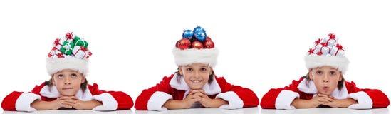Insegna di Natale con i bambini che portano i cappelli di Santa Immagini Stock