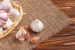 Insegna di orizzontale dell'aglio Eco che coltiva concetto Interi agli e chiodi di garofano nel canestro della paglia sul pezzo d Immagini Stock