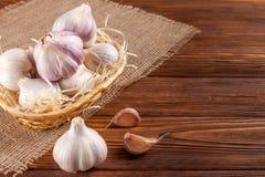 Insegna di orizzontale dell'aglio Eco che coltiva concetto Interi agli e chiodi di garofano nel canestro della paglia sul pezzo d Immagini Stock Libere da Diritti