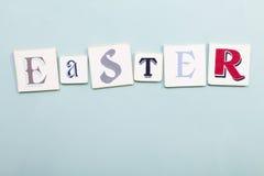 Insegna di Pasqua Parola scritta a mano delle lettere di colori Backgro blu-chiaro Fotografia Stock