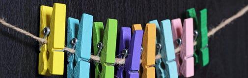 Insegna di piccole mollette da bucato colorate su una corda Fotografie Stock