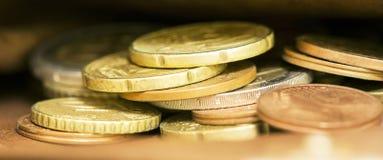 Insegna dorata del primo piano delle monete - concetto di risparmio dei soldi Fotografie Stock