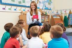 Insegnamento mostrando i flash card alla classe della scuola elementare Fotografia Stock Libera da Diritti