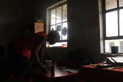 Insegnante africano del villaggio da uno scrittorio nello Swaziland rurale Fotografia Stock