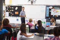Insegnante alla parte anteriore di classe in una lezione della scuola elementare fotografie stock