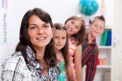 Insegnante allegro e parecchi allievi Fotografia Stock