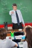 Insegnante arrabbiato Pointing At Schoolboy in aula Immagini Stock Libere da Diritti
