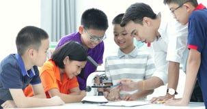 Insegnante asiatico che si espande allo studente nella classe di Biologia con il microscopio video d archivio