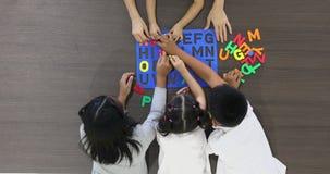 Insegnante asiatico e studenti che giocano insieme il giocattolo variopinto di puzzle di alfabeto, concetto per ricreazione stock footage