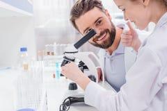 Insegnante barbuto che esamina piccolo studente che lavora con il microscopio in laboratorio Fotografia Stock