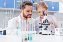 Insegnante barbuto che esamina piccolo studente che lavora con il microscopio in laboratorio Fotografia Stock Libera da Diritti