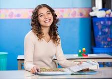 Insegnante With Book Sitting allo scrittorio Immagine Stock
