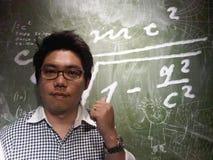 Insegnante caucasico con il suo punto del dito di colpo di uso di vetro alla lavagna Fotografia Stock