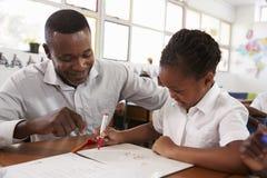 Insegnante che aiuta la ragazza al suo scrittorio, fine della scuola elementare su Fotografia Stock