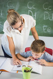 Insegnante che aiuta un ragazzo con il suo compito in aula Immagini Stock