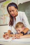 Insegnante che aiuta un ragazzo con il suo compito in aula Immagini Stock Libere da Diritti