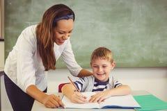 Insegnante che aiuta un ragazzo con il suo compito in aula Immagine Stock Libera da Diritti