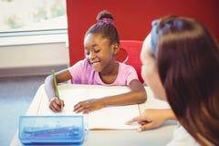 Insegnante che aiuta una ragazza con il suo compito in aula Immagine Stock