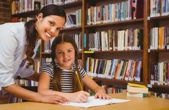 Insegnante che assiste bambina con compito in biblioteca Fotografie Stock