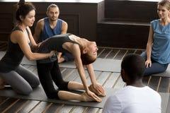 Insegnante che assiste donna che impara nuova posa di yoga all'addestramento del gruppo Fotografia Stock Libera da Diritti