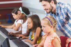 Insegnante che assiste le scolare nell'apprendimento del computer immagini stock