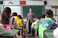Insegnante che dà una lezione ai bambini in un'aula cinese Fotografie Stock