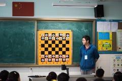 Insegnante che dà una lezione di scacchi ai bambini in un'aula cinese Fotografia Stock