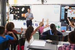 Insegnante che indirizza gli allievi in una lezione della scuola elementare Fotografia Stock