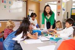 Insegnante che insegna ai bambini elementari con il gioco del blocco nella classe Immagine Stock Libera da Diritti