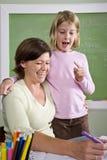 Insegnante che insegna al giovane allievo in aula Immagini Stock Libere da Diritti