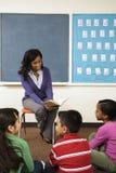 Insegnante che legge agli allievi fotografie stock